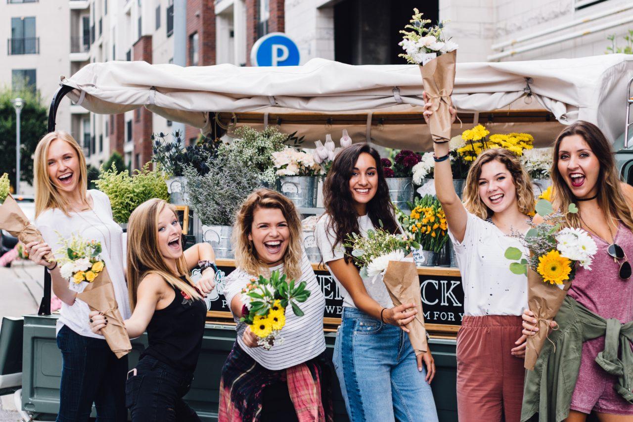 笑顔で花をプレゼントする女性たち
