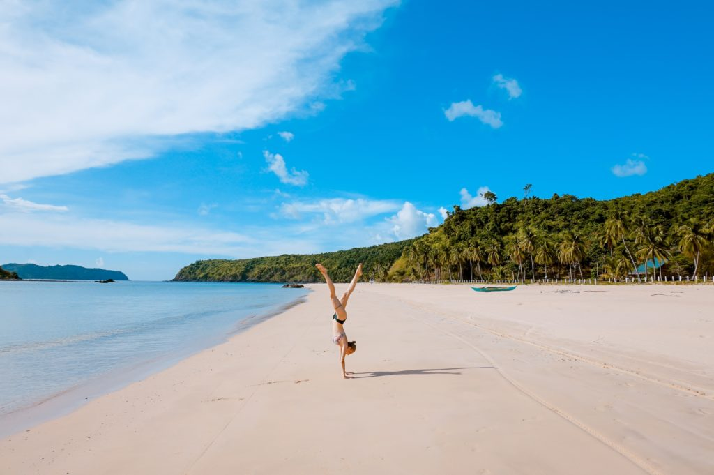 海辺でヨガの逆立ちのポーズをする女性