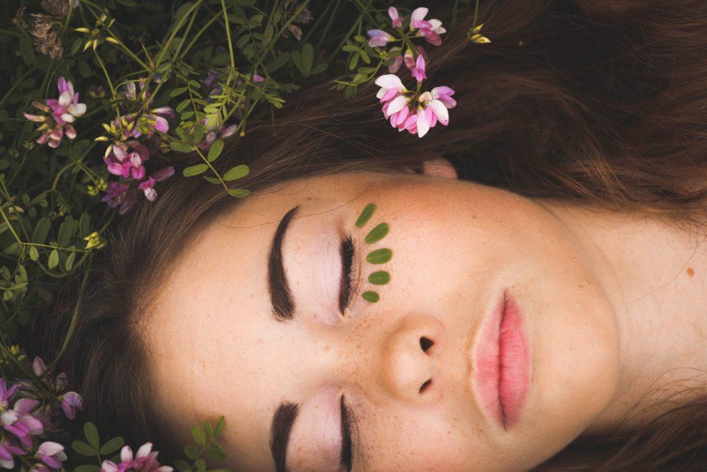 美肌の女性が植物の中で寝ている