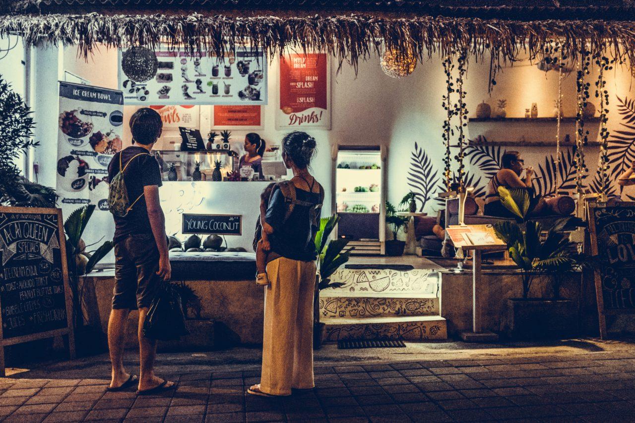 南国の屋台で買い物をする男女