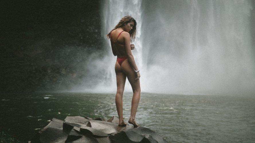 スタイルの良い女性が川で佇んでいる