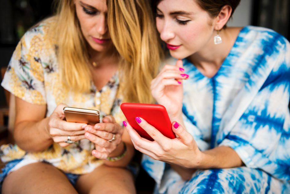 携帯電話の設定をする2人の女性