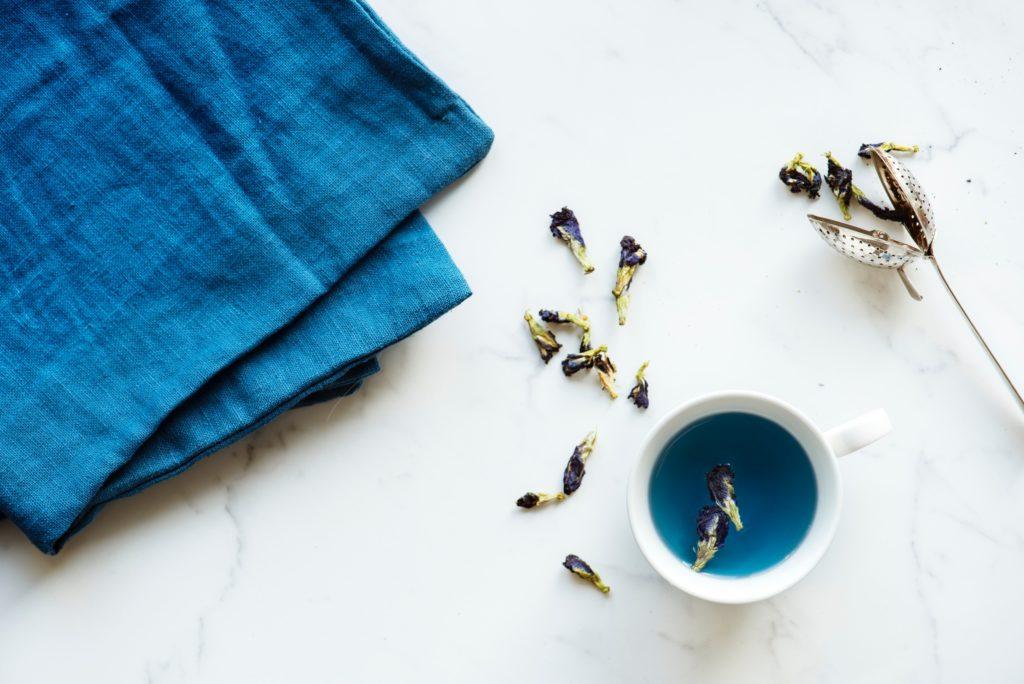 バタフライピーの青いお茶と花が入ったカップ