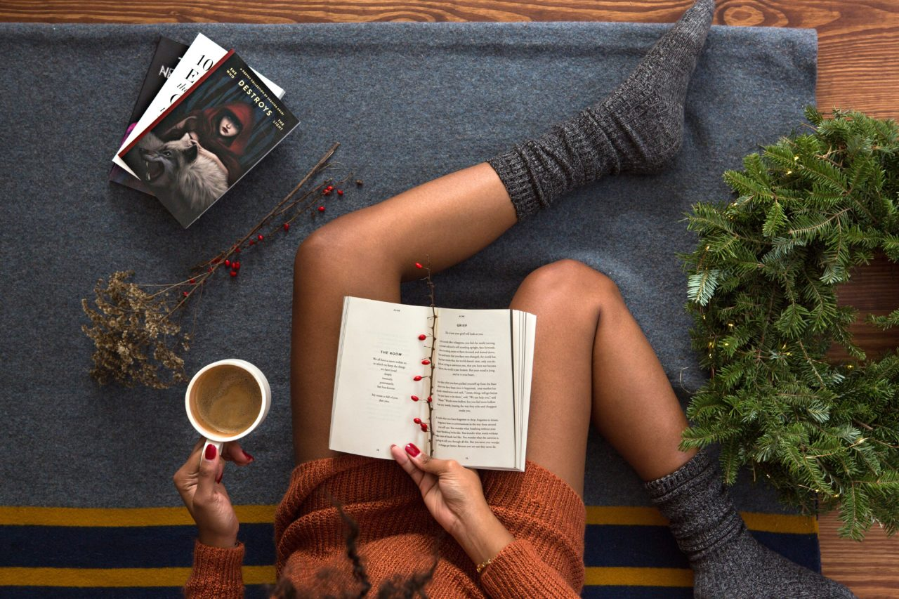 靴下をはいて本を読みながらリラックスする女性の足元