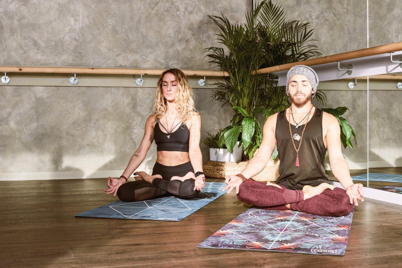 ヨガマットの上で瞑想をしている男女2人