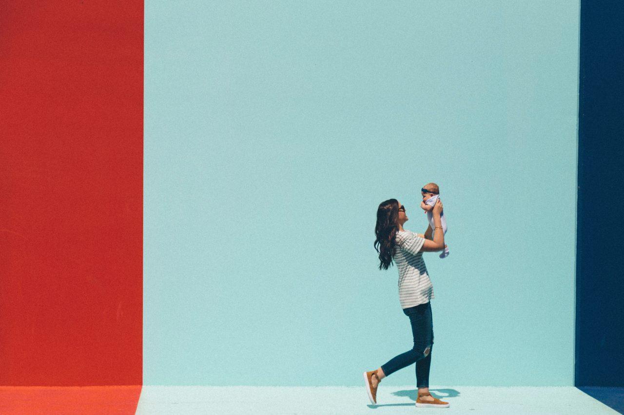 赤ちゃんを抱いて歩く産後の女性