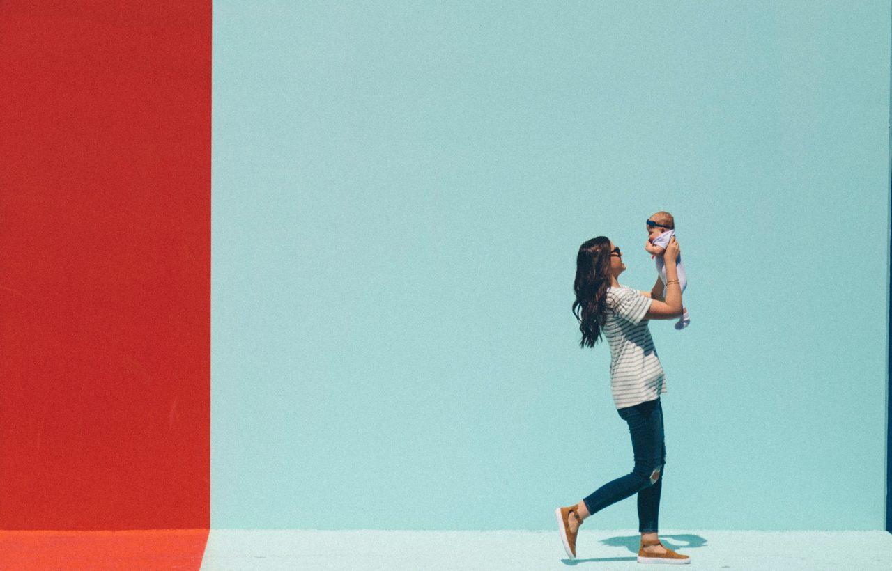 子供を抱っこしながら歩く女性