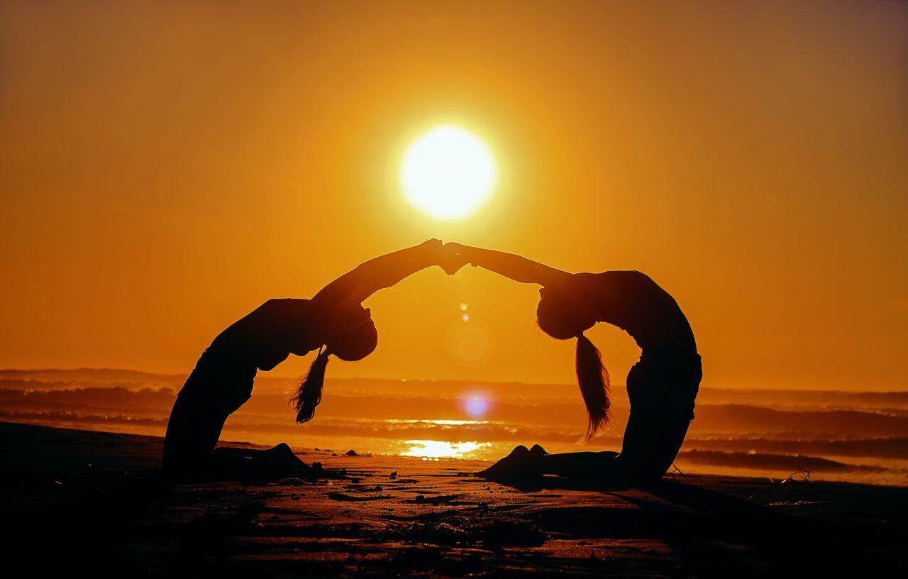 ヨガポーズをビーチで行う女性2人