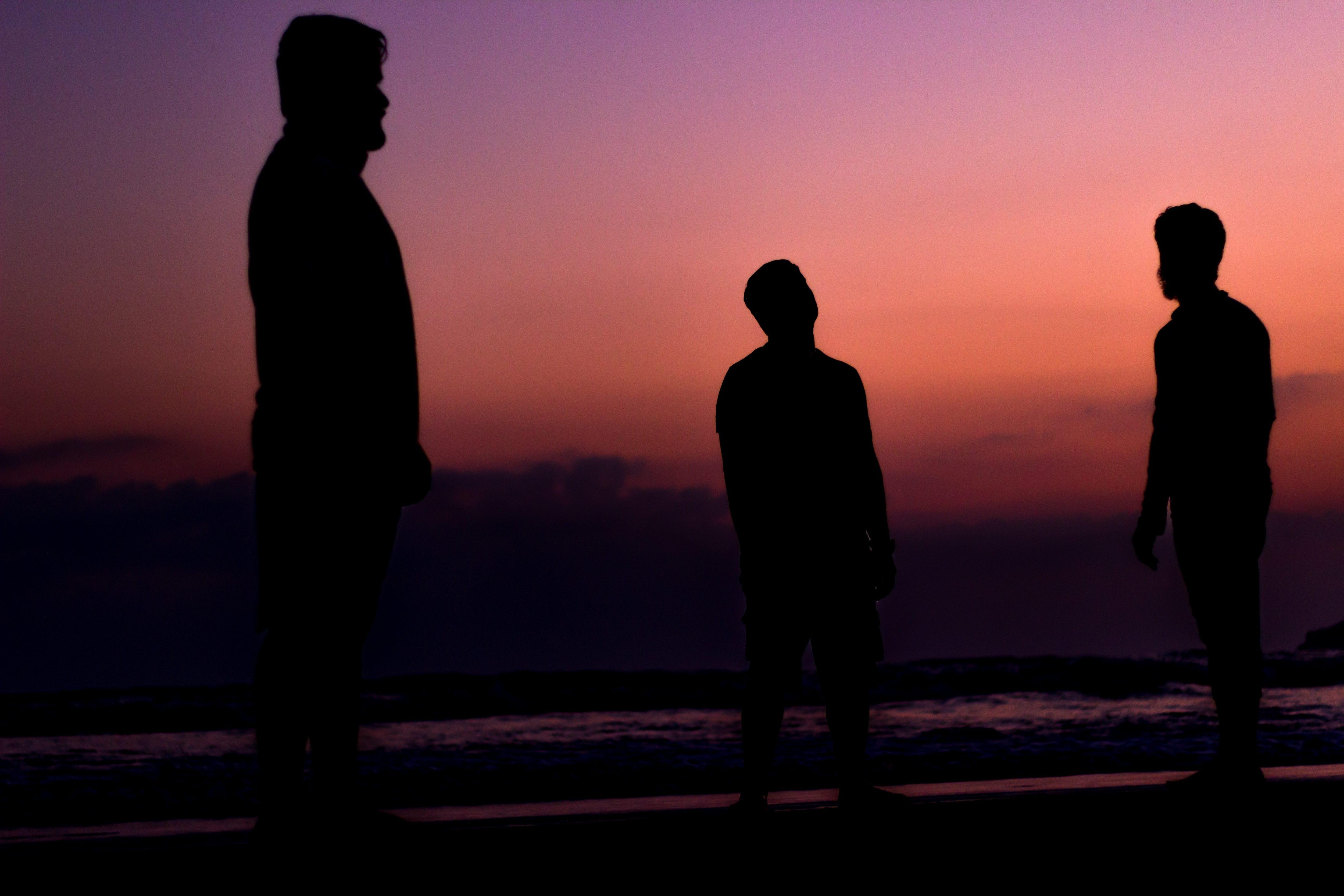 瞑想するように立つ中年男性3人