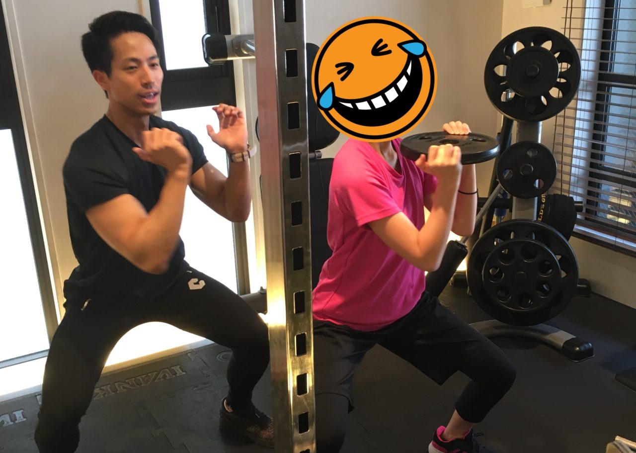 スクワットをする女性とトレーナー